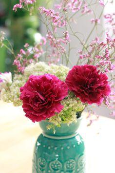 detailfoto van roze anjers en witte bloemen in een turquoise vaasje