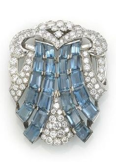 An art deco aquamarine and diamond brooch, circa 1930. Composed of two rivers of rectangular-cut aquamarines on a transitional and baguette-cut diamond-set open-work shield-shaped plaque; estimated total aquamarine weight: 10.00 carats; estimated total diamond weight: 5.25 carats; mounted in platinum #ArtDeco #brooch
