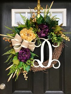 New item!! This gorgeous door wreath is ready to grace your front door! Made up on a 18 grapevine wreath with moss, mixed greens of ferns, ivies, hydrangea leaves and ficus leaves. Gorgeous deep purple and cream peonies with cream cat tails and beige berries makeup this adorable