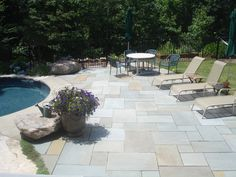 "the ""cobble stone"" pavers around this in-ground liner pool create"