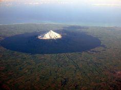 In 1881, a circular area with a radius of six miles from the summit of Mount Taranaki was protected as a Forest Reserve. With intensively-farmed dairy pasture reaching right up to the mostly-circular park boundary, the change in vegetation is sharply delineated in satellite images.   Photo by Jon Sullivan