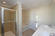 The master bath in the Dillon floor plan features dual vanity sink, standing shower, and separate garden tub.