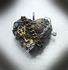Steampunk Pendant - In Chains - A piece I made for myself. The heart is polymer clay, which I wrapped in vintage and new chains, and embellished with a gold plated heart and key, and vintage watch parts. Hand painted background of gold and copper mica powders and the back is sealed with a coat of resin. Size - 4cm x 4cm and 1cm deep. I am happy to make something similar as a commission for between £27.99 and £30.00 depending on the amount of detail wanted.