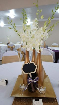 Wedding centerpieces: Spray Gold wine bottles (Valspar Metallic Gold) (Chateau St. Michelle are the best wine bottles by shape and height. .see photo) flowers: orchids