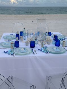 mediterranean dinner party decor. white table cloth with different blue tints. coral pieces for table decor.