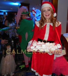 CHRISTMAS PARTY THEMED MISS SANTA CLAUS serving sweet treats or canapes for family fun events and parties