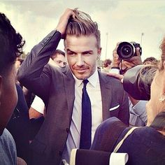 David Beckham wearing solid navy skinny tie, charcoal single breasted suit, white shirt, and white pocket square. Classic!