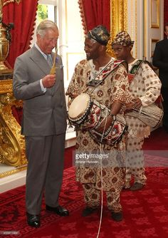 Prince Charles, Prince of Wales plays a drum held by musician Ayan De First of Oduduwa Talking Drummers at a reception for members of Britain's West African origin community at Clarence House on July 20, 2011 in London, England.