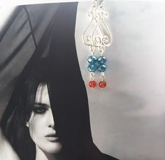 Stunning faceted sea blue crystal dropped from a silver chandelier piece finished with fiery tempered Carnelian. Simple feel good every day earrings.  Measures approx 2.5 inch  All items are handmade in house, quite literally my home where I design collections my mood board to fit the theme I want to offer onto Vie Beads the brand. All beads are sourced within the UK.