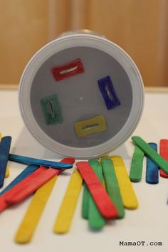 Colorful popsicle sticks and en empty coffee can to work on preschool fine motor skills #finemotor #childdevelopment
