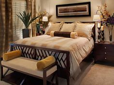 Warm neutrals with golden accents draw you into this warm, intimate master bedroom. The slight sheen on the drapery panels and bedding add a luminous quality, and the linear details of the fabrics and furniture are caught by the light from the wall mounted arc sconces on either side of the room. A true retreat within the home, this cozy spot will make for a memorable 'staycation.'