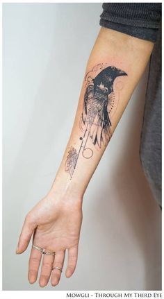 Graphic style raven tattoo on the right forearm.