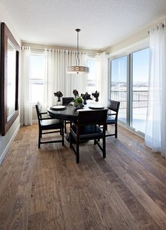 Dark hardwood floors in modern dining space with white drapes
