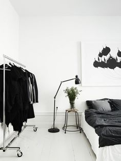 A beautiful black and white apartment bedroom — perfect home for your clothes, flowers, and of course art