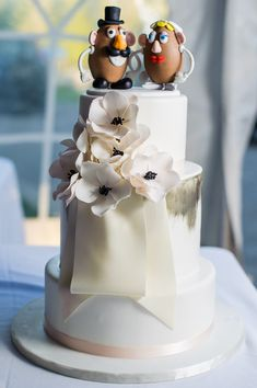 white wedding cake with flower accessory and mr and mrs potato head cake toppers #weddingcake #caketopper #weddingchicks http://www.weddingchicks.com/2014/01/28/creative-canuck-wedding/