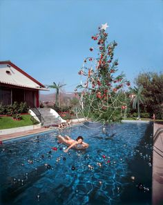 by Slim Aarons. Rita Aarons, wife of photographer Slim Aarons, on a lilo in a swimming pool decorated for Christmas, Hollywood, 1954 Black Christmas Trees, Christmas In July, Retro Christmas, Christmas Photos, Family Christmas, Xmas Tree, Aussie Christmas, Tropical Christmas, Celebrating Christmas
