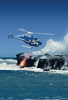 Blue Hawaiian Helicopter flying over molten lava flowing into the ocean in Volcanoes National Park, The Big Island, Hawaii.