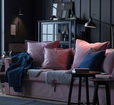 Un salón con un sofá cama de tres plazas en color rosa claro lleno de cojines de ese mismo color.