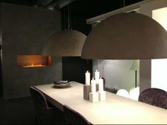 Stoere tafel met betonlook blad en een schouw met betonlook.