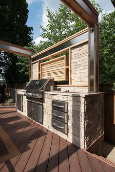 "With a built-in barbeque, stone countertops, stacked stone enclosure, and stone & cedar privacy screen, this kitchen has all the fixings! From ""Decked Out"" project ""The BBQ Deck"". Deck design by Paul Lafrance Design."