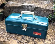 Vintage Revelation tackle box from Western Auto Store. Teal green ( turquoise blue ) metal tool or tackle box with inside white plastic compartment for extra storage. Original red sticker on front ( Revelation, Western Auto Store ). In excellent vintage condition, appears to have been used very little if at all?? Top has rubber off white handle with raised measuring guide ( 12 ). PAT.NOS.161360 AND 3171566. Very minor wear to paint with no rust & clean inside ( like new). Closes tightly! ...