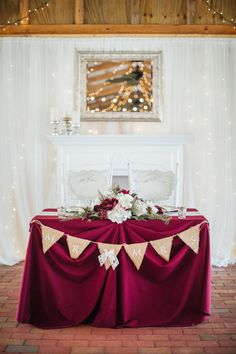 Rustic Barn Wedding Bride and Groom Sweetheart Table with Burlap Pennant Sign, Burgundy Tablecloth, White Lace Draping and String Lights, and Low Cream and Marsala with Greenery Centerpiece