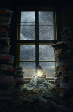 Boy reading in front of rainy window