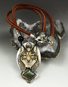 Is Himself Lynx necklace made by Rebecca Jurgens of LandSArts. Sterling Silver, Labradorite, Black Agate and Porcelain. The Lynx cabochon is made by the talented Laura Mears.