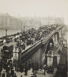 People crossing London Bridge around the turn of the century (could be anything from 1890 to 1910).