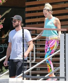 Together: Miley's tattoos were on show in her sleeveless top while her bearded boyfriend wore a baseball cap pulled down over his hair