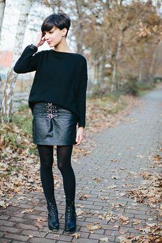 Pull large à col droit, jupe courte en cuir à boucles, collant en laine noir