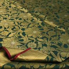 Deep bottle green #silk plays host to swirling floral #motifs in gold and silver to create a bewitching effect. The wide gold ribbon border is trimmed with a smear of kumkum to add a hint of colour. Paisley and rudraksh motifs add a playful touch to the richness of the gold pallu. A plain bottle green blouse with running border is all that is needed to make this a perfect Kanjivaram for any bride. For Kanjivarams in this alluring green, visit Sarangi. Code 540126104.