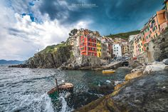 Riomaggiore during a storm   Riomaggiore is a village in the province of La Spezia, situated in a small valley in the Liguria region of Italy. It is the first of the awesome Cinque Terre, a UNESCO World Heritage Site. I took this picture during a short thunderstorm, when the dark clouds were full of rain and the sea was very rough.  Cinque Terre   Liguria - Italy © www.chiarasalvadori.com