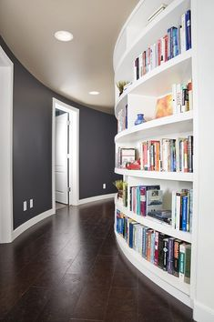 i love absolutely everything about this hallway--the curved shape, the built-in bookshelf, the cobalty/grey wall with bright white trim, and lastly, the dark hardwood floor.  win all around!