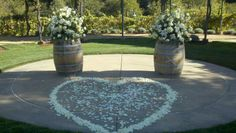 Sweetheart ceremony in the wine country. Instead of a traditional altar, wine barrels were adorned with fresh blooms, and vows were exchanged in the center of the heart made of fresh flower petals.