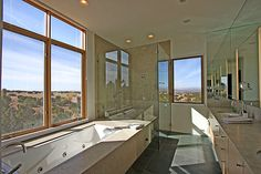 Natural light and a wall of mirrors brighten this master bathroom.