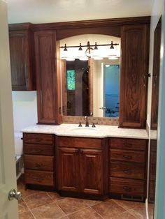 Bathroom Remodel: Dark stained wood cabinets, white stone counter tops, bronze faucet