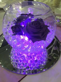 Fish bowl wedding centrepiece for purple themed weddings.  Purple illuminated beads, cadburys purple roses and Ivory butterfly. Available to hire for your wedding in Swansea, Neath, port talbot, Bridgend, porthcawl, Llanelli, Carmarthen and surrounding areas of South Wales from affinity event decorators www.affinityeventdecorators.com