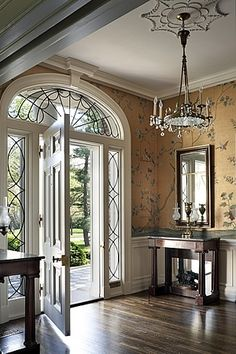 love the wallpaper and notice the ceiling medallion and the glass design in the arch above door.