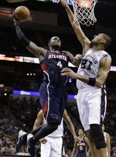 Atlanta Hawks' Paul Millsap (4) drives as San Antonio Spurs' Tim Duncan (21) during the second half of an NBA basketball game, Monday, Dec. 2, 2013, in San Antonio. San Antonio won 102-100. (AP Photo/Eric Gay)