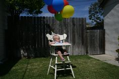 Birthday boy in his AFK high chair decorated with balloons