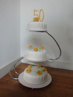 Een mooie klassieke bruidstaart op een moderne standaard. Voor een 50 jarig huwelijk. Met goud gespoten marsepein rozen en als topper een 50 van chocolade. kijk eens op 123gebak.nl