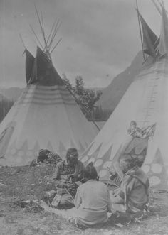Blackfoot Indians sitting with James Willard Schultz in front of tepees, 1912?