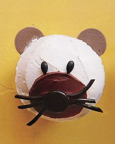 Transform a basic cupcake into a mouse using buttercream frosting, black licorice, and chocolate wafer cookies.