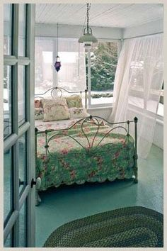 Sheers blowing in the breeze with braided rugs and soft cool colors. Sleeping Porch.