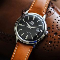 Orient Bambino a minimalist design that shouldnt look out of place with anything.
