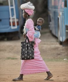 I love this photo by Bill McDad of a beautiful Mom from Gambia (Africa) looking very put together & in multitasking mode as she carries her little one, her tote, & a head bundle into town. She looks powerful & stunning in her pink outfit & jewelry, & her baby is equally dressed up, complete w/ earrings & bangle bracelets. I also love how the baby blue colored buses in the background compliment the baby blue sash around her waist that holds her beloved child. Nice composition, great color…
