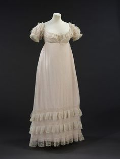This sheer muslin evening dress (1821-23) demonstrates the survival of neo-classical elements of women's dress into the early 1820s. While heavier fabrics in brighter colours appeared in day dress, white remained fashionable for evening.
