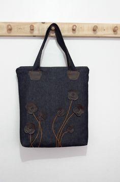 Bolsa em jeans, com detalhe em flores feitas de corino.