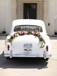 "Drive off in style inside a 1961 Bentley decked with a pretty floral swag and stamped with a ""Just Married!"" window decal."